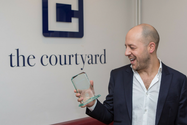 Marcos White, owner of The Courtyard holding the award for completing 500 Invisalign cases